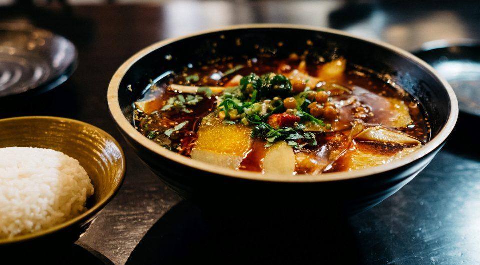 Azjatycka zupa z kawałkami ryby i zielonym groszkiem